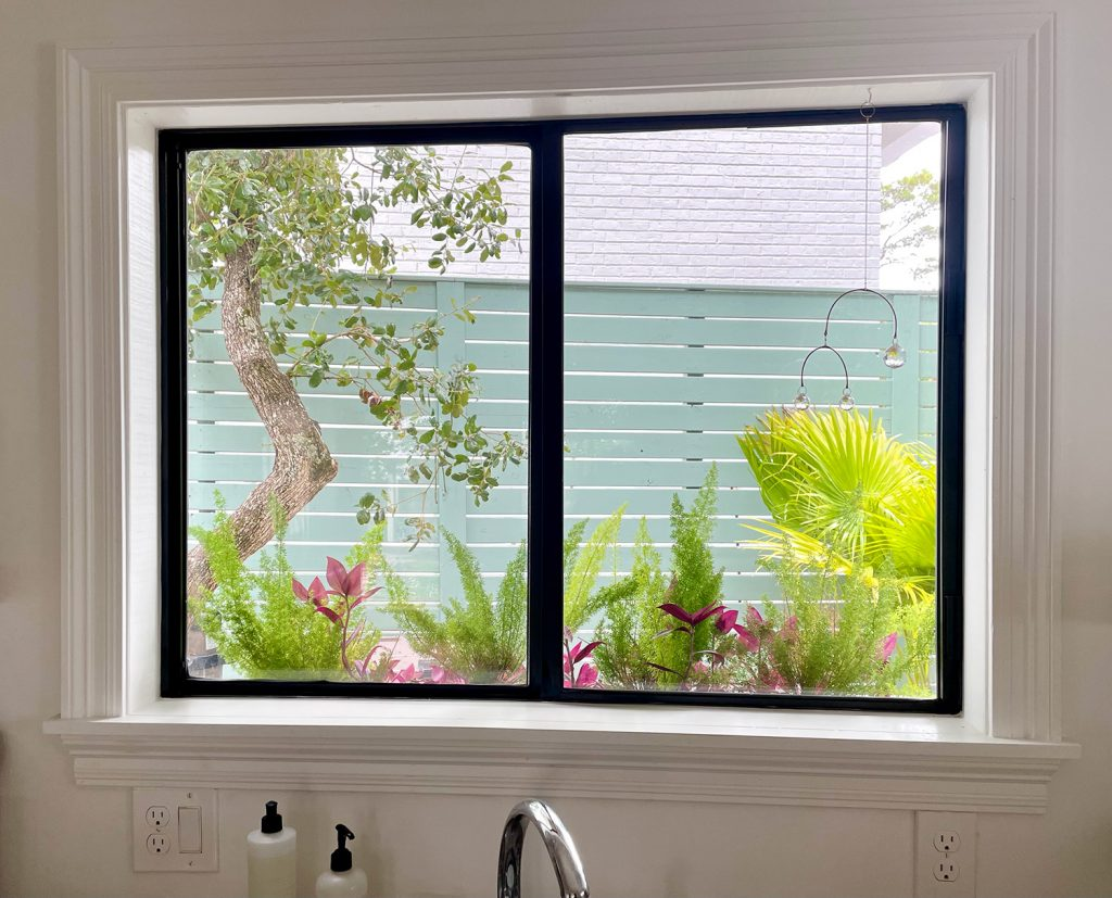 View Through Kitchen Window With Window Box And Tropical Plants