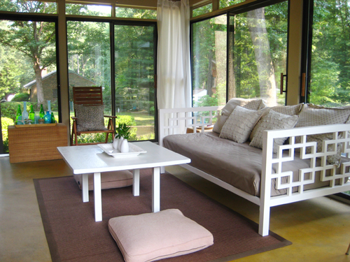 glass doored sunroom with golden yellow stained concrete floors and white daybed and coffee table