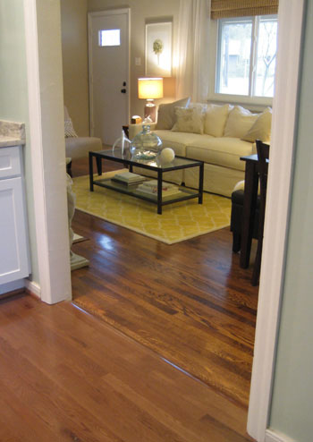 clean hardwood floor showing transition between original oak hardwood and engineered hardwood installed to closely match