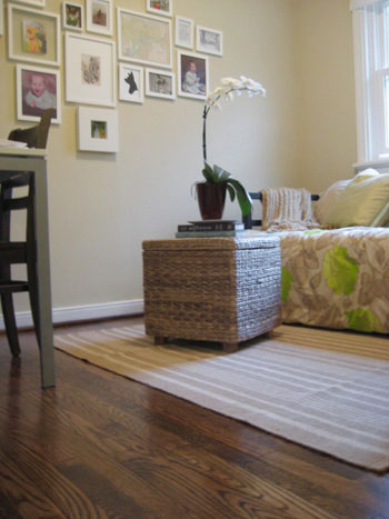clean hardwood floor with dash & albert striped rug and woven wicker ottoman with orchid