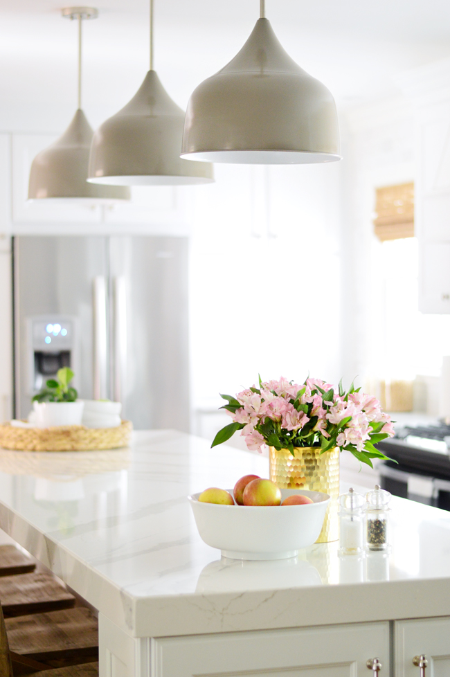 white kitchen with large gray pendant lights shades of light