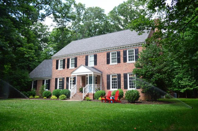 irrigation system watering lawn of brick colonial home