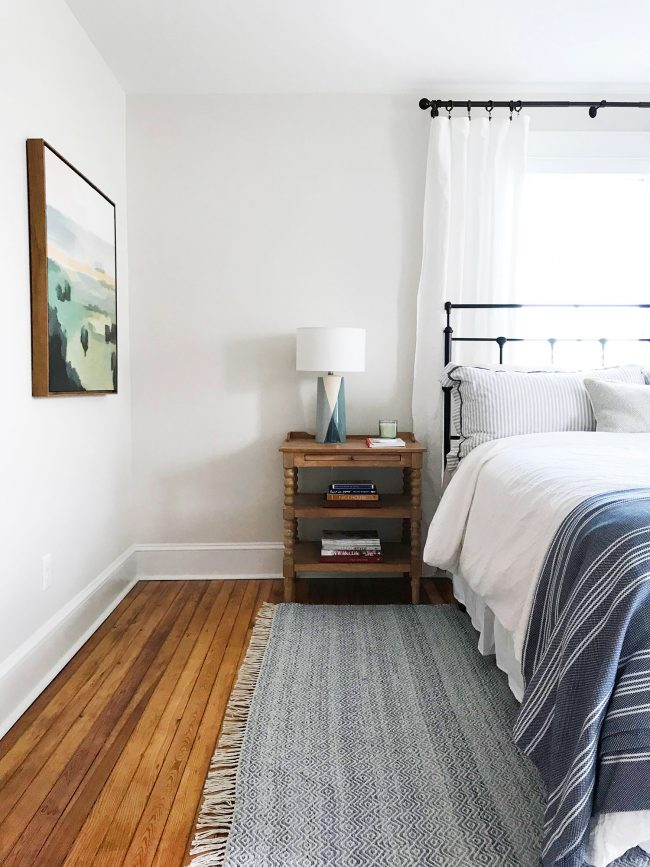 metal headboard in beachy blue bedroom with pine floors