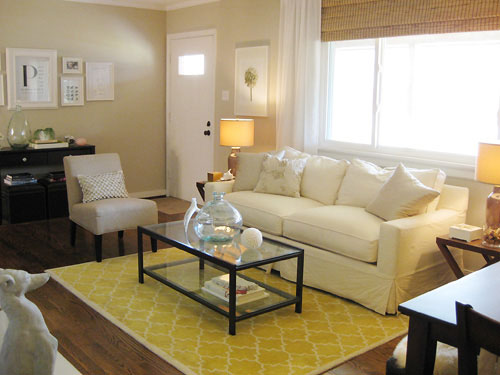 neutral living room with white sofa graphic yellow rug and glass and iron coffee table